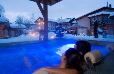 Paar entspannt im Außenwhirlpool am Abend