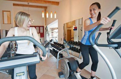 Zwei junge Frauen machen Sport auf Crosstrainern