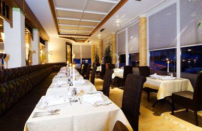 Restaurant mit weißen Tischen und schwarzen Stühlen