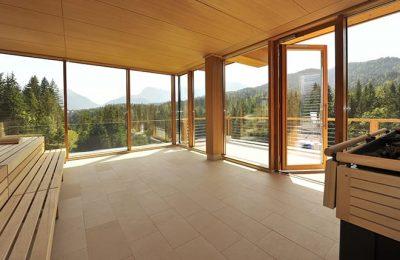 Sauna mit großer Glasfassade und Blick auf umliegenden Wald