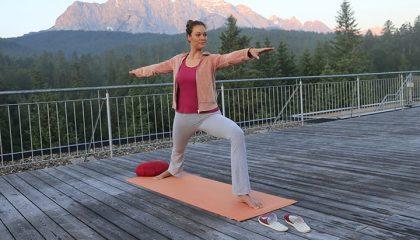 Frau macht Yoga auf einer Terrasse