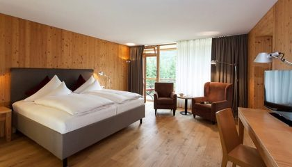 Bett und Wohnraum in der Suite im Gartenflügel