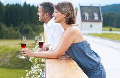 Paar genießt Rotwein vor dem Hotel