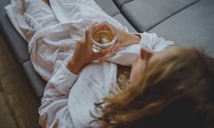 Frau in weißem Bademantel entspannt mit Getränk