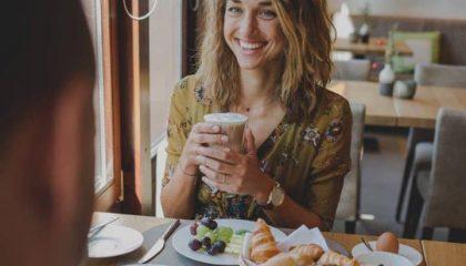Frau trinkt Latte Macchiato beim Frühstück