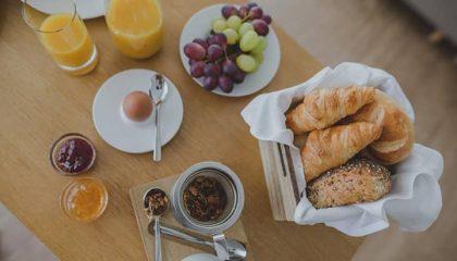 Gedeckter Frühstückstisch mit Kaffee, Orangensaft und Croissants