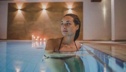 Frau kühlt sich im Pool ab