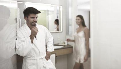 Paar in weißen Bademändeln im Bad