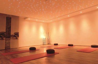 Orange beleuchteter Yogaraum mit Matten