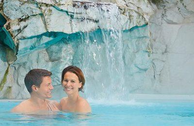 Paar im Pool unter Wasserfall