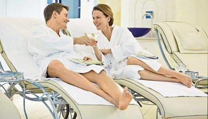 Paar relaxt auf Liegen neben Pool