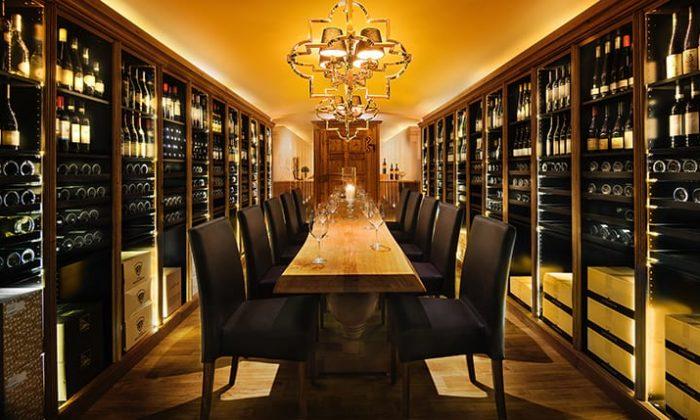 Tisch im Weinkeller neben zahlreichen edlen Tropfen