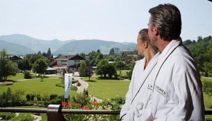 Paar in weissen Bademänteln auf dem Balkon