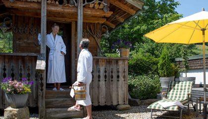 Paar in weißen Bademäntel im Garten vor Hütte