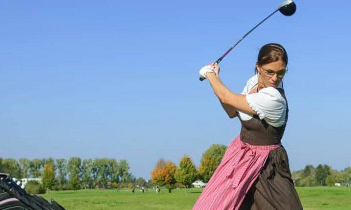 Frau im Dirndl spielt Golf