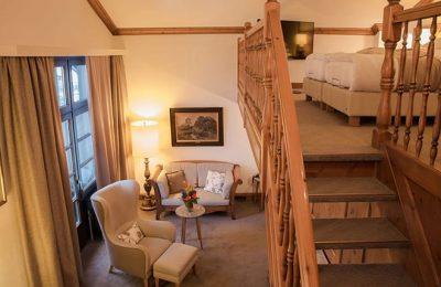 Wohnraum und Treppe in der Maisonette Suite