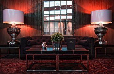 Braun-schwarze Couch neben zwei großen Lampen