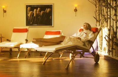 Frau entspannt auf Liege im Ruheraum