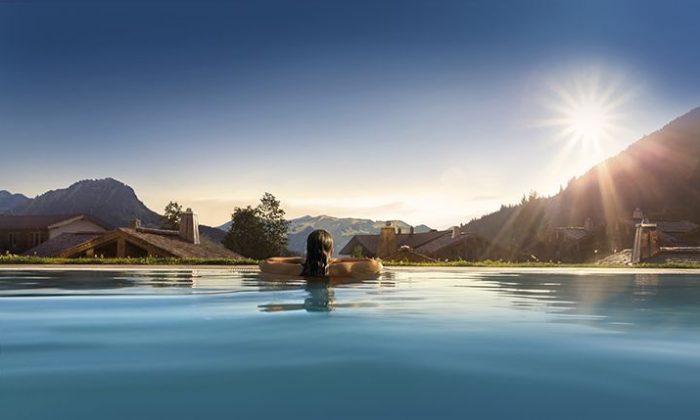 Frau schwimmt im Inifnity Pool vor Alpenkulisse