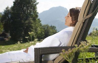 Frau liegt in Liegestuhl im Garten