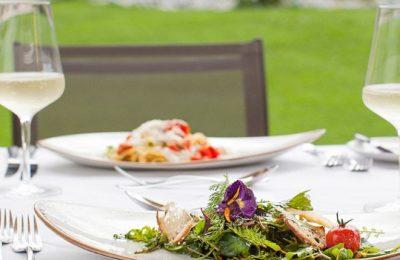 Essen auf der Terrasse neben Weingläsern