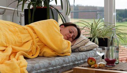 Frau in gelbem Bademantel entspannt
