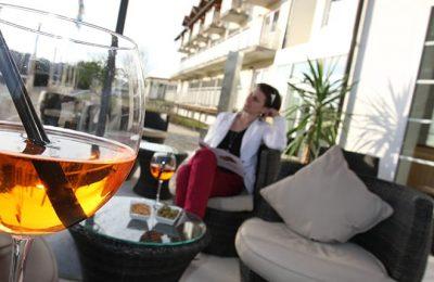 Frau genießt Auszeit auf Terrasse mit Getränk