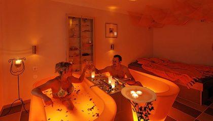 Mann und Frau stoßen mit Sekt beim Wärmebad an