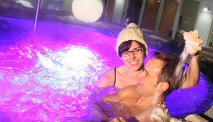 Paar badet im beleuchteten Whirlpool am Abend