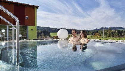 Paar badet im Whirlpool an sonnigem Tag