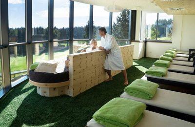 Mann und Frau in weißen Bademäntel entspannen im Moosraum