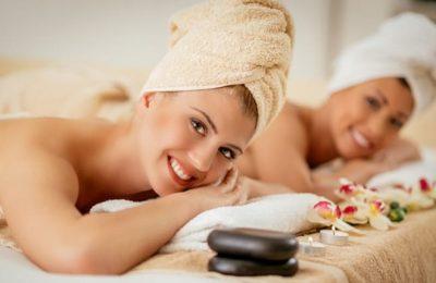 Zwei Frauen mit weissen Handtüchern genießen Massage