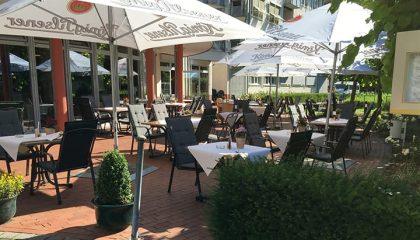 Sitzgelegenheiten und Sonnenschirmen im Biergarten