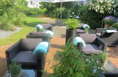 Braune Sessel mit grünen Handtüchern im Garten
