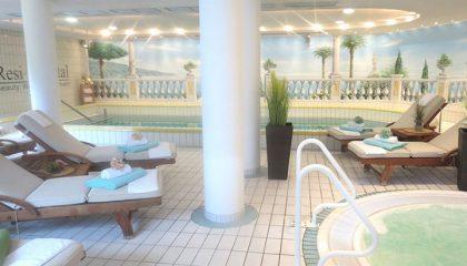 Weisse Liegen und Whirlpool neben Indoor Pool