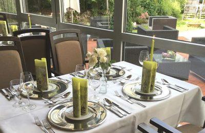Gedeckte Tische neben Glasfassade im Restaurant