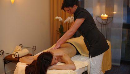 Frau wird massiert bei Wellnessanwendung