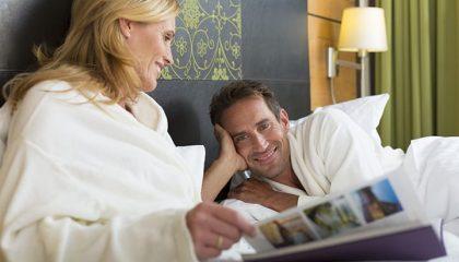 Paar entspannt gemeinsam in weißen Bademänteln