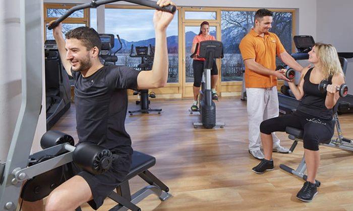 Menschen trainieren an modernen Geräten im Fitnessraum