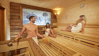 Zwei Frauen und ein Mann genießen einen Saunagang