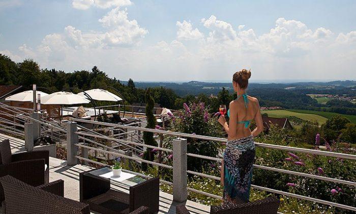 Frau mit Drink auf dem Balkon