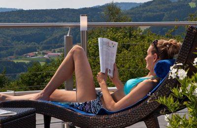 Frau relaxt in Liege auf der Terrasse