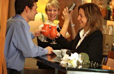 Paar und Barkeeperin an der Bar
