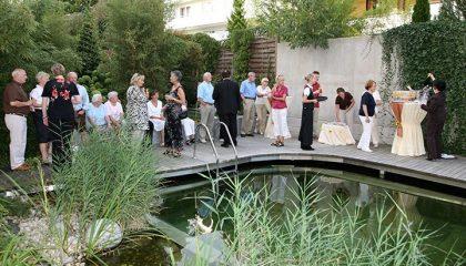 Gruppe Menschen stoßen an am Naturschwimmbad