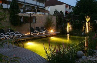 Beleuchtetes Naturschwimmbad am Abend