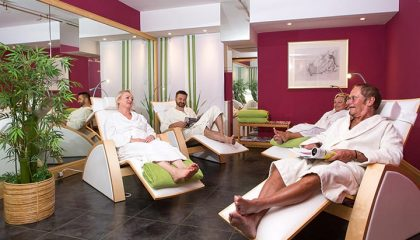 Menschen in weißen Bademäntel entspannen im Ruheraum