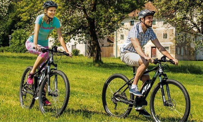 Mann und Frau fährt auf Mountainbikes durch die Natur