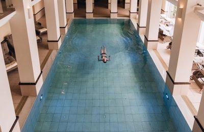 Frau schwimmt Bahn im Indoor Pool im Romantik Hotel Diedrich
