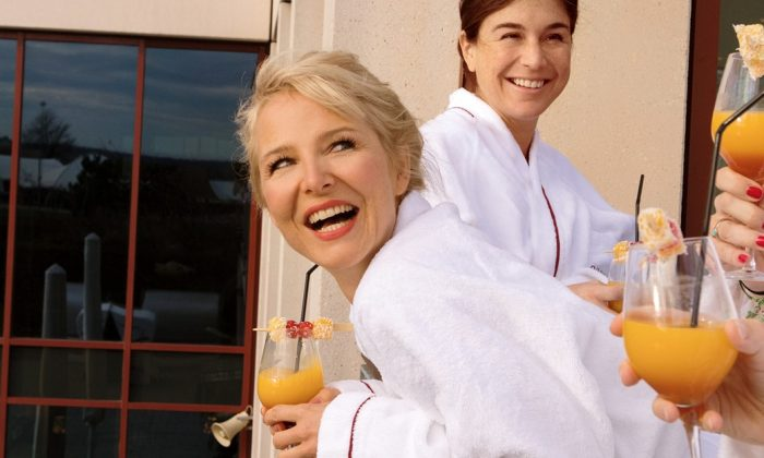Drei Freundinnen in weißen Bademänteln genießen erfrischende Drinks