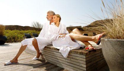 Paar in weißen Bademänteln entspannt im Garten zwischen den Dünen